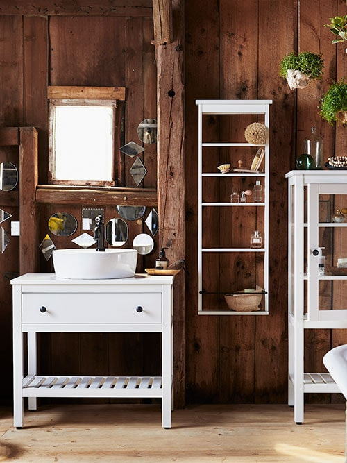 A white HEMNES/TÖRNVIKEN open wash-stand, against a rough dark wooden wall decorated with lots of small mirrors.