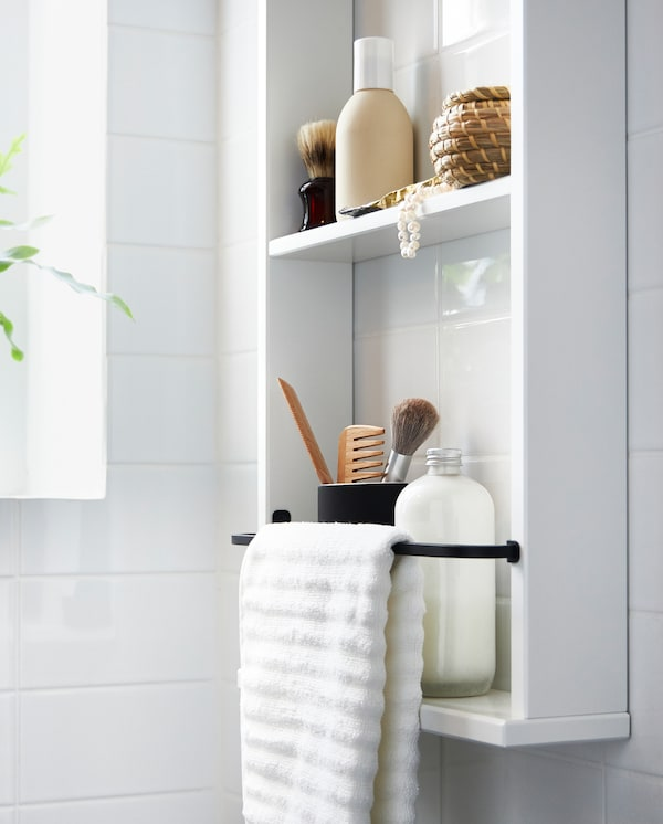 A white HEMNES wall shelf holding bottles, makeup and a white towel on a black metal rack attached to the shelf.