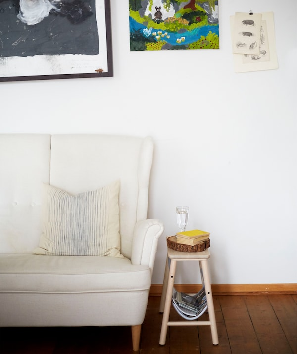 A white high-backed sofa and small wooden stool against a white wall with artwork.
