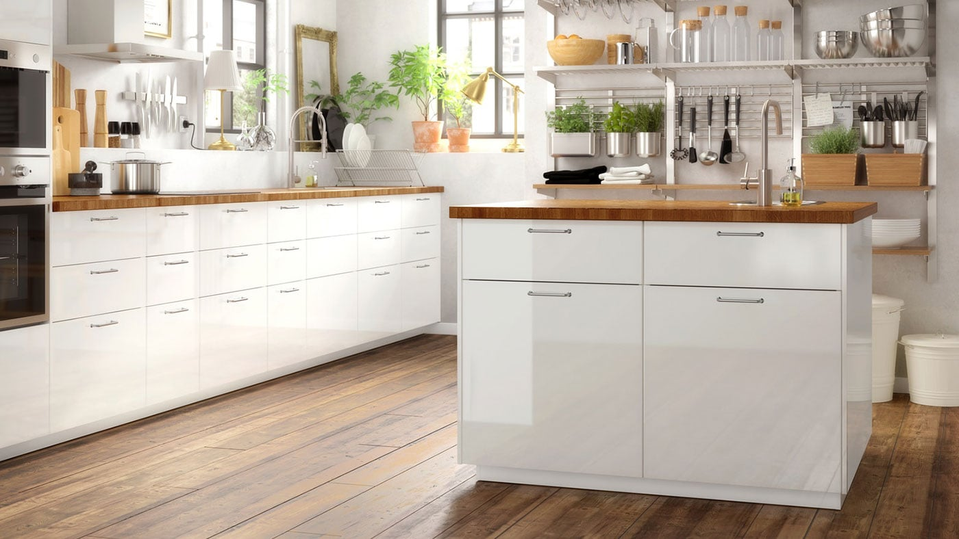 A white high-gloss RINGHULT kitchen with wooden worktop and metal, slimline handles.