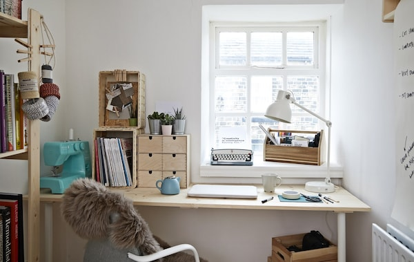 A white home office with desk and office chair, with a sewing machine and an old fashioned typewriter on the window sill.