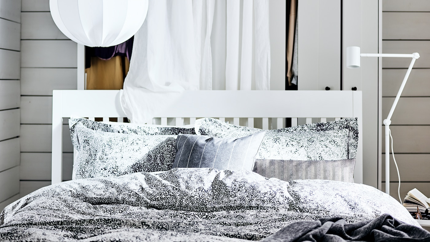 A white IDANÄS bed in a white bedroom with a curtain hanging behind, a pendant lamp above it, covered with grey bed linen.