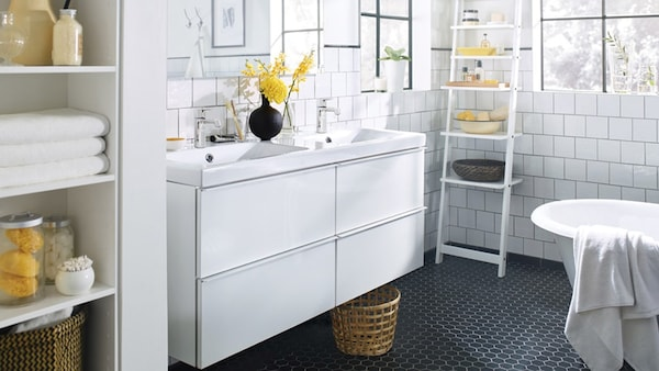 A white IKEA bathroom with a sink cabinet and ladder storage.
