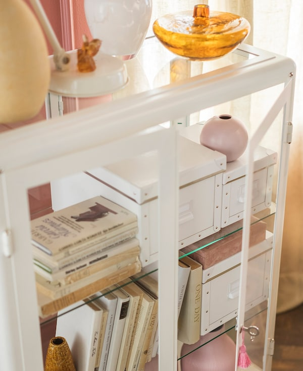 A white IKEA FABRIKÖR glass cabinet filled with books, boxes and vases.