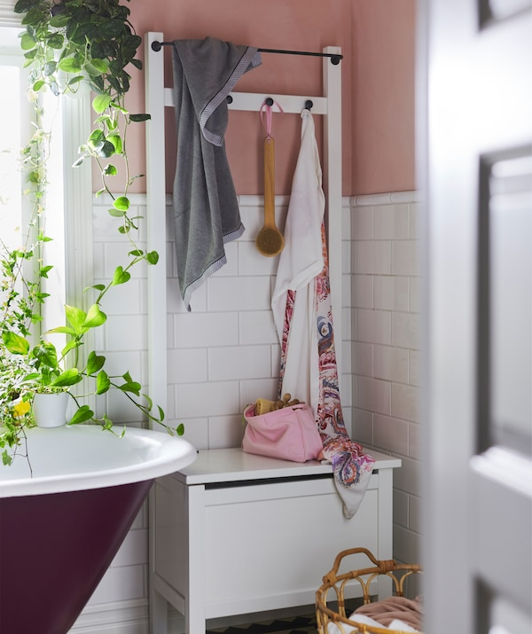A white IKEA HEMNES storage bench with hooks and a rail next to a bath and plants.