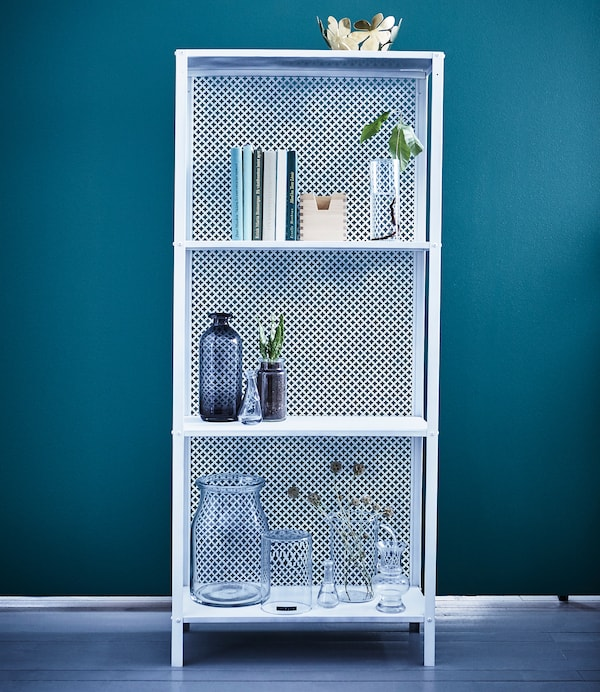 A white IKEA HYLLIS shelving unit is decorated with books, plants, and glass vases.