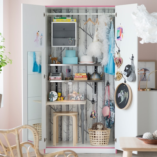 A white IKEA PAX wardrobe unit turned into a children's toy storage area with shelves, basket and stool inside.