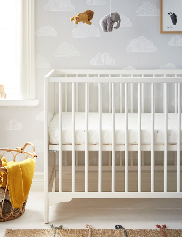 A white IKEA SOLGUL rocking cot on white wooden floorboards with SOLGUL yellow blanket and a natural textile rug.