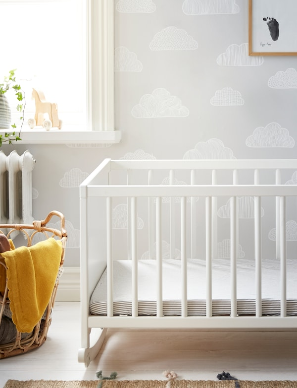 A white IKEA SOLGUL rocking crib on white wooden floorboards with SOLGUL yellow blanket and a natural textile rug.