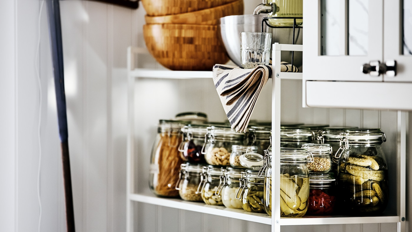 A white JONAXEL shelving unit holding jars of preserved vegetables, kitchenware and wooden serving bowls beside a wall cabinet.