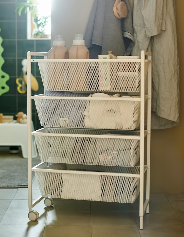 A white JONAXEL trolley with four mesh baskets and two wheels, holding folded towels, clothes and laundry detergents.