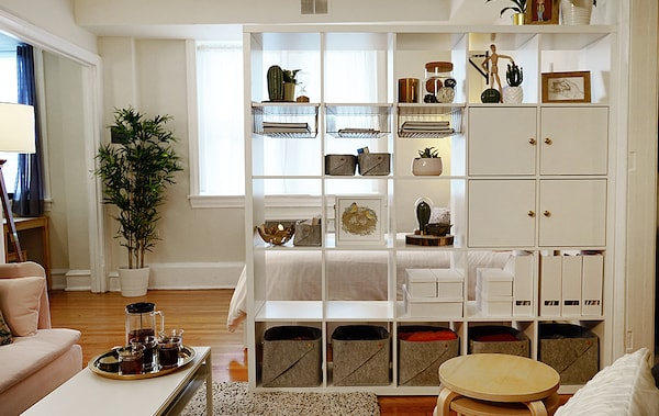 A white KALLAX bookshelf with boxes and doors is used as a room divider between a bedroom area and living room.