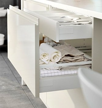 A white kitchen drawer filled with textiles