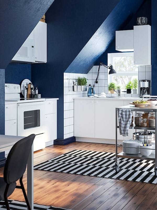 A white kitchen in a loft with blue walls and white cabinets. A kitchen trolley stands on a striped rug in the centre.