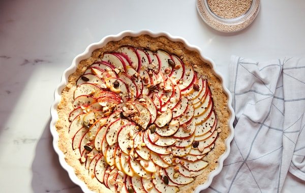A white kitchen towel with a grey, graphic pattern and a pie covered with thin apple slices in a white VARDAGEN pie dish.