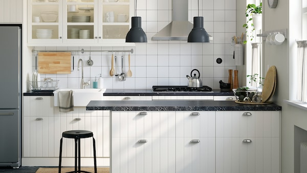 A white kitchen with a mix of wooden and glass doors, two gray pendant lamps and a black mineral-effect worktop.