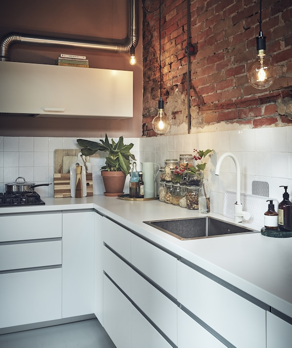 A white kitchen with an exposed brick wall.