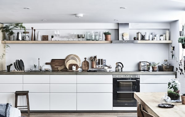A white kitchen with concrete worktops and shelving.