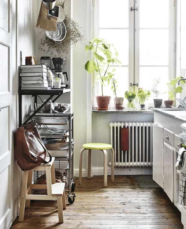 A white kitchen with open storage and a step stool.
