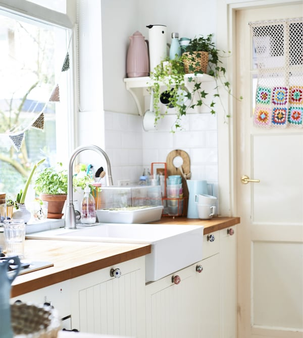 A white kitchen with pastel pots and plants on a shelf.