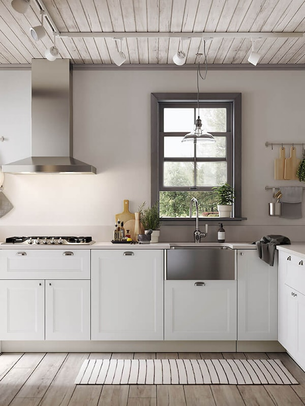 A white kitchen with white drawers and cabinets with glass doors and a stainless steel sink with a visible front.