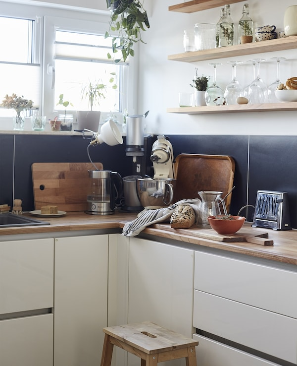 A white kitchen with wooden worktops and shelving.