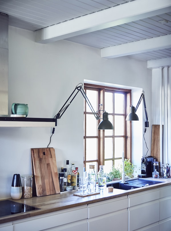 A white kitchen with worktops and lamps.