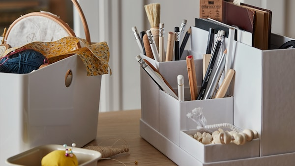 A white KUGGIS box with no lid is placed beside a white TJENA desk organizer. The KUGGIS box contains sewing supplies and the TJENA box contains writing utensils such as a notebook and pencils.