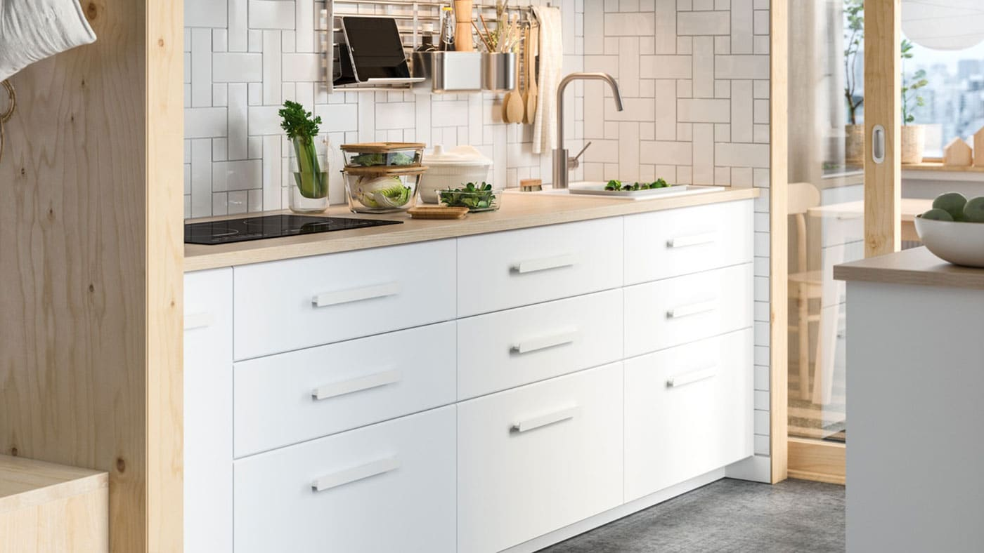 A white KUNGSBACKA kitchen with wooden worktop and white, slimline handles.