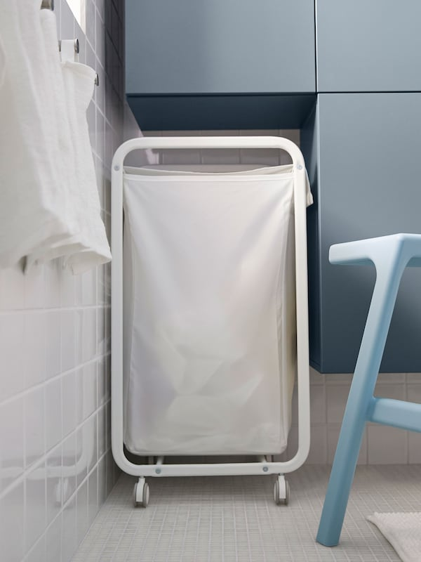 A white laundry bin tucked into the space between the cabinet and the wall in a small bathroom.
