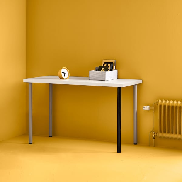 A white LINNMON table top with silver and black legs in the corner of a bright yellow room with a yellow radiator beside it.