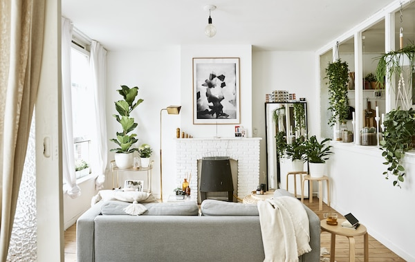 A white living room with sofa, fireplace, plants and stools used as side tables.