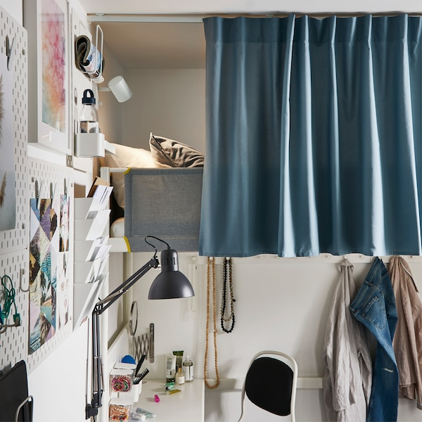A white loft bed that is mostly covered by a blue curtain that's attached to a curtain track in the ceiling.
