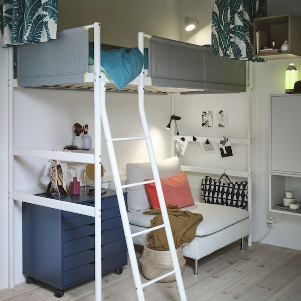 A white loft bed with grey guardrails, and under it is a white 1-seat sofa section, a blue drawer unit and a laptop support.