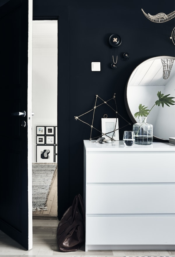 A white MALM chest of drawers with a round mirror above, against a black wall.
