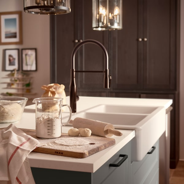 A white marble effect worktop, a black mixer tap, dark grey drawer fronts and a wooden chopping board with flour and dough.