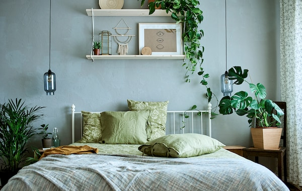 A white, metal framed bed with green bedding, plain and patterned in a room decorated with plants and art.