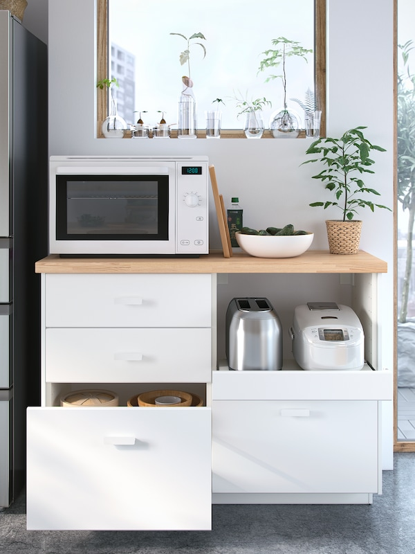 A white microwave stands below a window on top of a wooden worktop with four white drawers below, one is open.