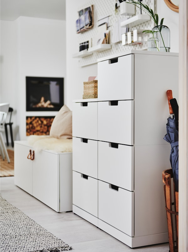 A white NORDLI chest of drawers standing against a white wall near the hallway area of an open floor-plan home interior.