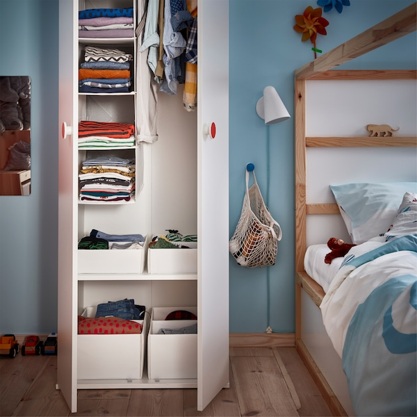 A white open closet with organised children's clothes, a bed in white and pine and a white wall lamp.