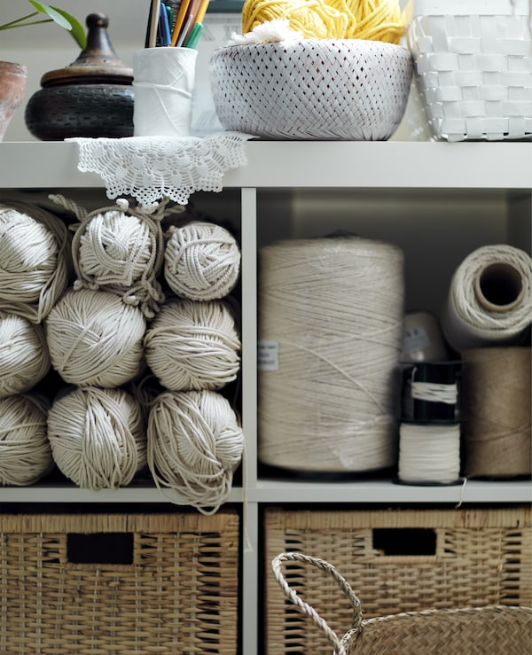 A white open shelving unit filled with craft supplies.