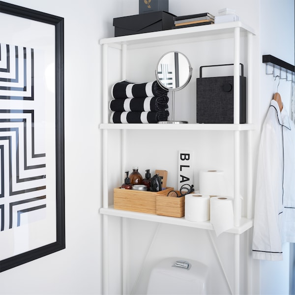 A white open storage that's placed above the toilet and transforms an often unused wall space into storage space.