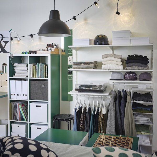 A white open wardrobe with wall-mounted sections with shelves and rails. Both folded and hanging clothes are stored here.