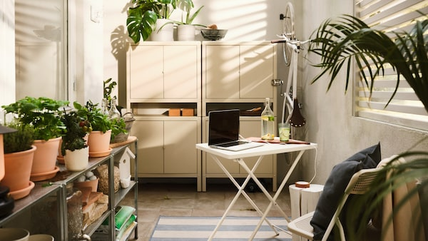 A white outdoor dining table with a laptop, four stacked beige steel cabinets, various plants and a hanging white bicycle.