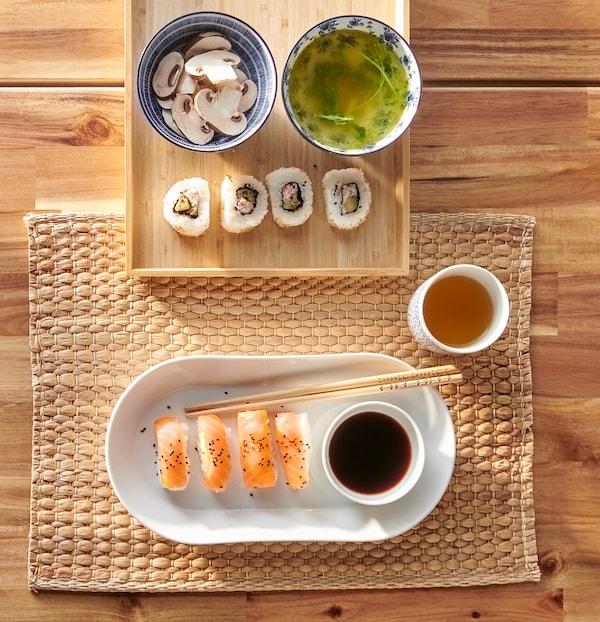 A white, oval plate with sushi, white and blue ceramic ENTUSIASM bowls with miso and mushrooms, a bamboo tray and place mat.