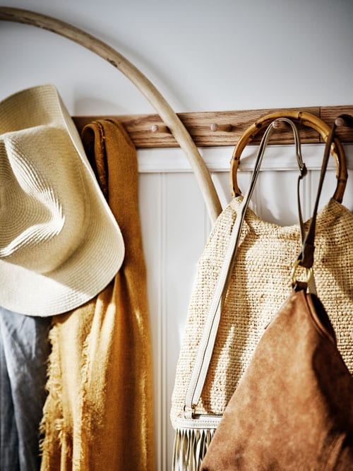 A white panelled wall with a row of light wooden hooks holding a hat, a scarf, some bags and a wooden hoop.