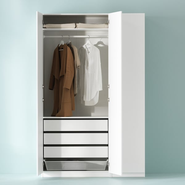 A white PAX wardrobe stands partly open. There are clothes hanging from a rail, drawers, shelves and a basket inside.