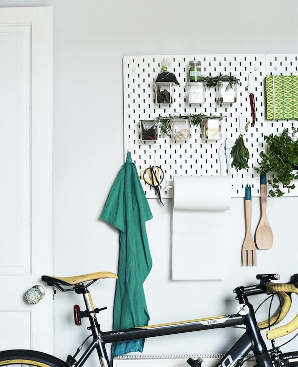 A white pegboard filled with tools and plants in a white room.