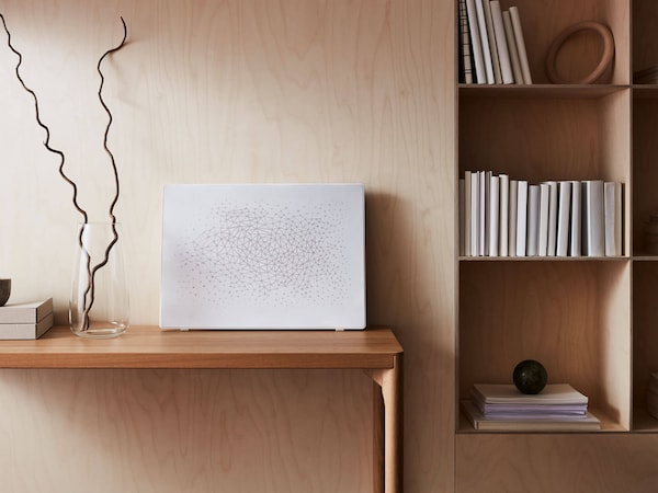 A white picture frame with a built in speaker sitting on a wooden desk with a wooden wall behind and a bookshelf next to it.