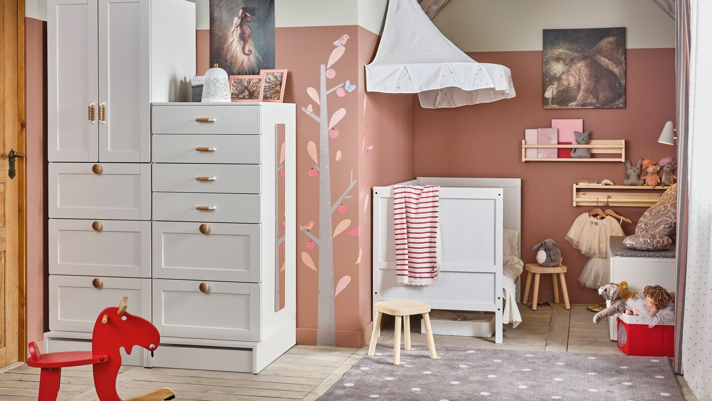 A white/pink traditional children's room with SMÅSTAD storage, a SUNDVIK crib, and FLISAT children's stools.